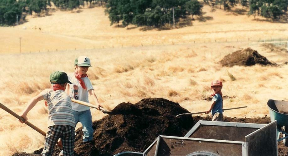 farmer boys shoveling compost on Capay farm